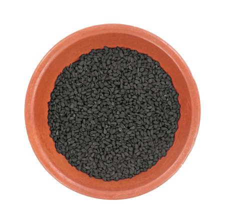 Top view of a small bowl with a portion of black caraway seeds on a white background.