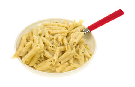 A serving of cooked pasta with garlic and parsley in a thick cream sauce on a small plate with a red handle spoon.
