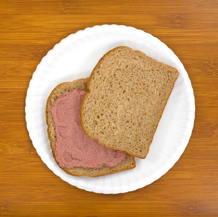 Top view of a potted meat sandwich with whole wheat bread on a white plate atop a wood table.