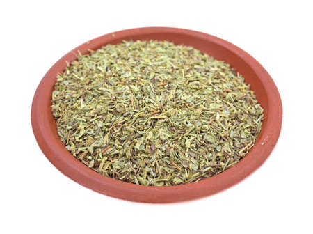 A portion of savory herb in a small bowl on a white background.