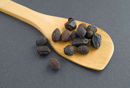 A wood spoon with saw palmetto berries on a dark background. Banco de Imagens - 31741675