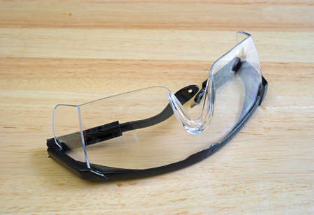 protective: A pair of plastic safety glasses atop a wood table top.