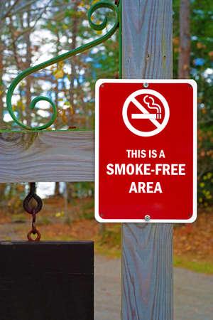 Een rood en wit rookvrij gebiedsteken op een houten post.