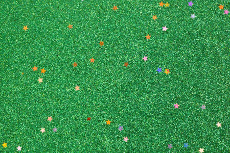 Close view of a green glitter background with small stars.