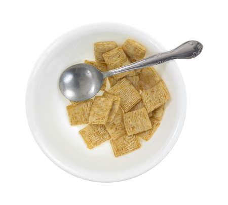 leftover: Top view of a bowl of leftover whole wheat cereal with a spoon on a white background.