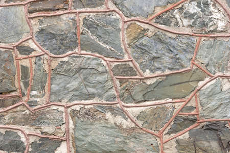 grout: A close view of an exterior stone wall with thick grout outlining the individual stones.