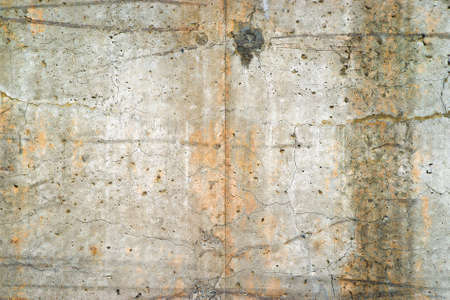gouged: An old poured concrete exterior retaining wall weathered and stained with age.