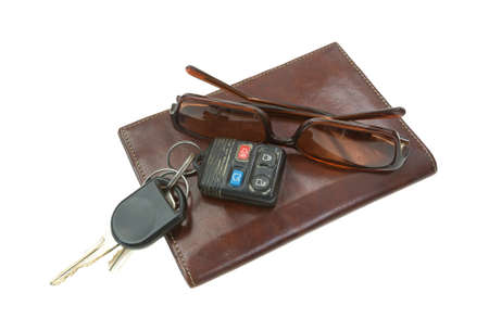 billfold: A pair of used sunglasses and car keys atop a leather billfold on a white background. Stock Photo