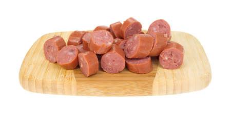 Several chunks of smoked sausage on a wood cutting board.