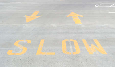 A bright yellow slow sign printed on concrete with arrows.