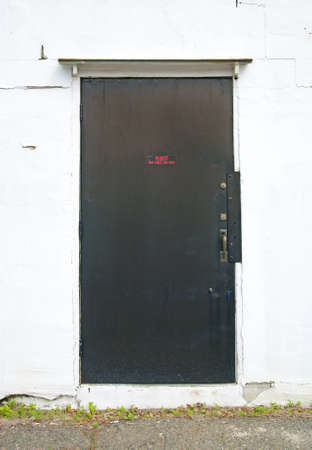 weed block: An exterior steel exit exterior door mounted into a concrete stucco wall
