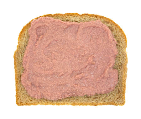 Top view of potted meat spread on a slice of whole wheat bread atop a white background. 版權商用圖片