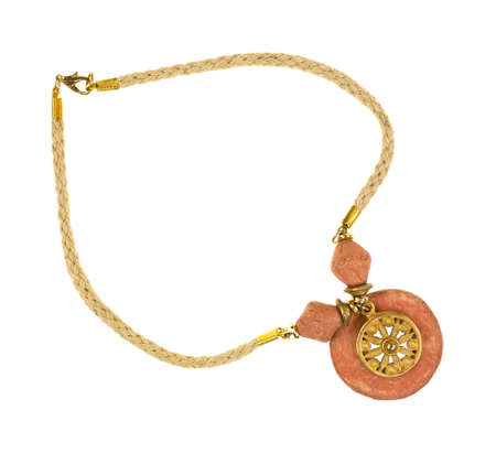 terra cotta: A terra cotta clay pendant with a gold symbol attached to a cord necklace.