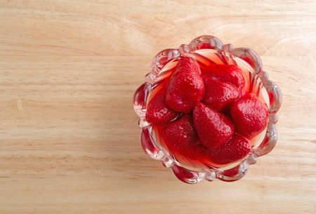 offset view: Top view of a glass bowl filled with canned strawberries in juice upon a wood table top.