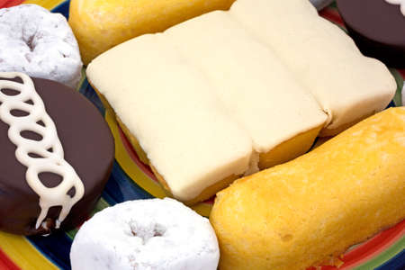 A very close view of junk food including powdered donuts, cream filled cakes, chocolate iced cakes and iced covered cakes on a dish.