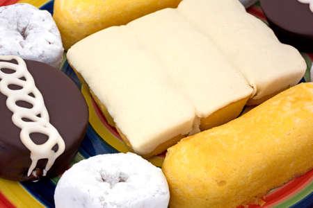 comida chatarra: Una visi�n muy estrecha de la comida chatarra incluyendo rosquillas en polvo, pasteles de crema lleno, tortas de chocolate helado y pasteles cubiertos con hielo en un plato.