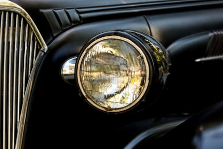 speedster: A headlight and partial grill of an old American speedster coupe.