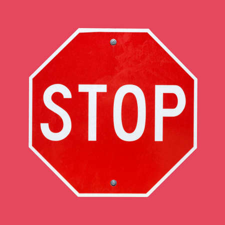 A bright red and white stop sign on a subdued red background.