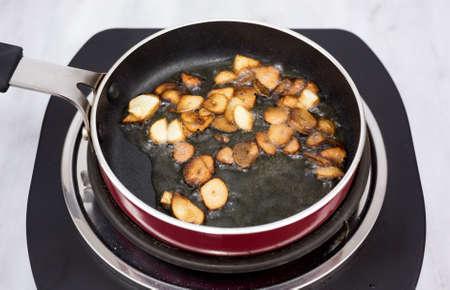 小型シングル バーナーにオリーブ オイルでスライスしたニンニクを小さなフライパン料理します。