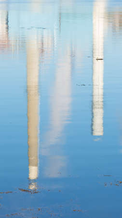The blurred reflection of two large smoke stacks on salt water with seaweed floating in the foreground.