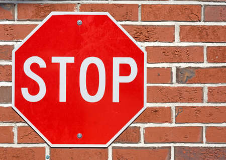 old sign: A bright red and white stop sign bolted to a brick wall.