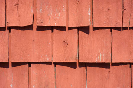 shrinkage: A very close view of old painted wood shingles that are curling with age and exposure to the sunlight.