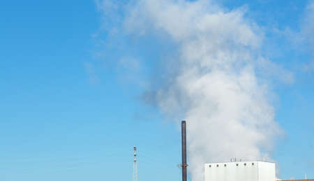 A large emission of steam rising from a factory against a bright blue sky with building and smokestacks in the foreground. Stock Photo