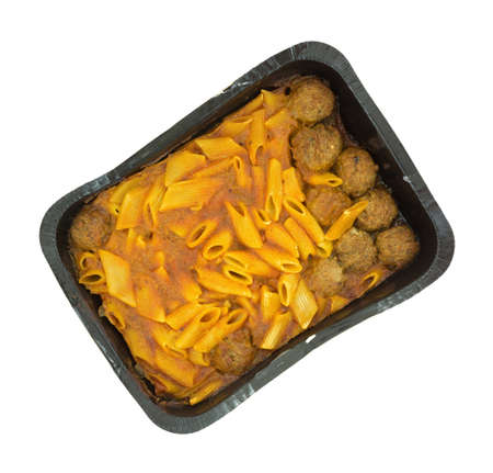 Top view of a very large serving of penne pasta in a tomato sauce with meatballs in a black tray atop a white background.