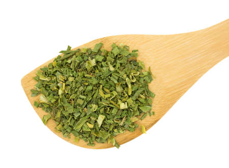 Top view of a wood spoon with a portion of chopped dried chives on a white background.