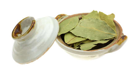 A small bowl filled with dried basil leaves plus a lid to the side on a white background.