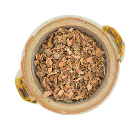 astringent: Top view of a portion of witch hazel bark in a small bowl atop a white background.