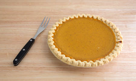 tines: A freshly baked pumpkin pie on a wood table with a fork.