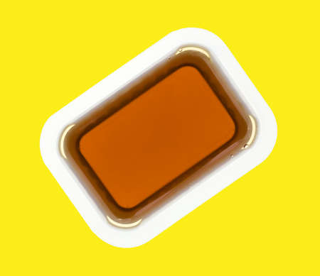maple syrup: A small plastic container of maple syrup on a bright yellow background.