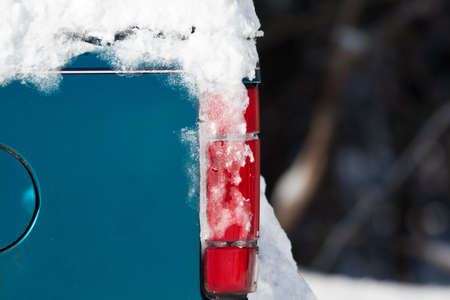 taillight: Snow covering parts of an old truck with a red taillight.