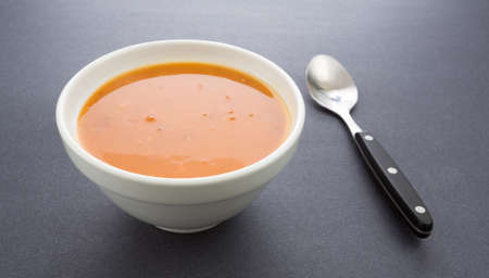 window light: A bowl of tomato bisque soup with a spoon to the side on a dark background illuminated by window light.