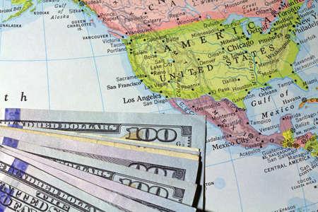 conceptual maps: Una vista parcial de billetes de cien d�lares en la cima un viejo atlas que muestran los Estados Unidos y los pa�ses vecinos.