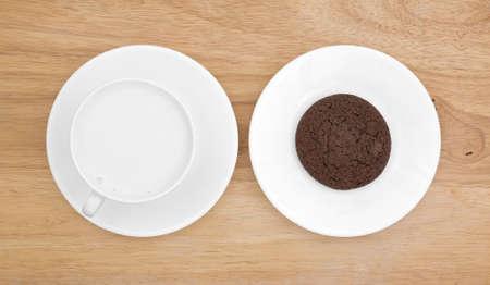 cookie chocolat: Vue de dessus d'un biscuit au chocolat sur une soucoupe avec du lait entier dans une tasse de caf� au sommet d'un plateau de table en bois