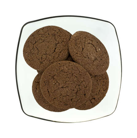 atop: Top view of a group of chocolate cookies in a translucent bowl atop a white background. Stock Photo