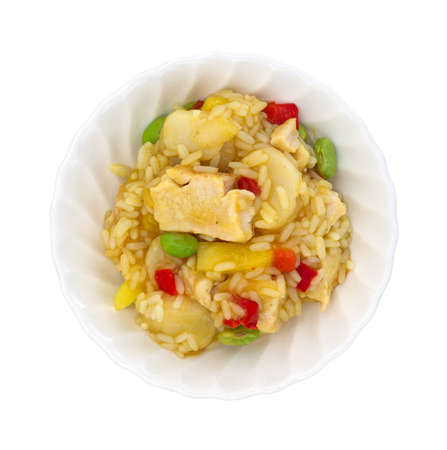 red peppers: Top view of a bowl of chicken with red peppers, edamame, water chestnuts in a pineapple sauce on a white background.