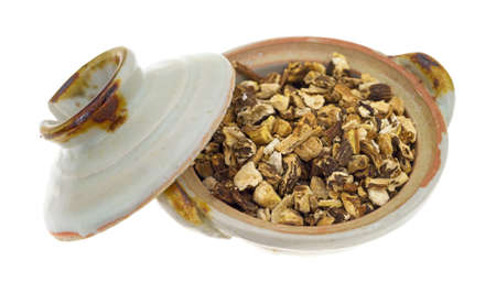 botanical remedy: A small bowl filled with dried chopped dandelion root with the lid to the side on a white background.