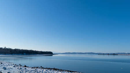 sears: A view of the tip of Sears Island in Searsport Maine during the winter with ice covered coastline in the foreground and the distant port in the background. Stock Photo