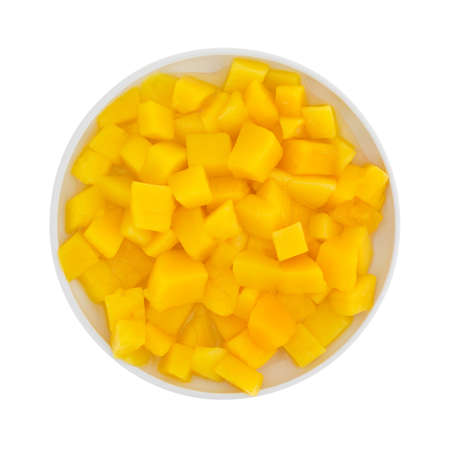 Top view of a small dish filled with canned mango in small chunks isolated on a white background. 版權商用圖片