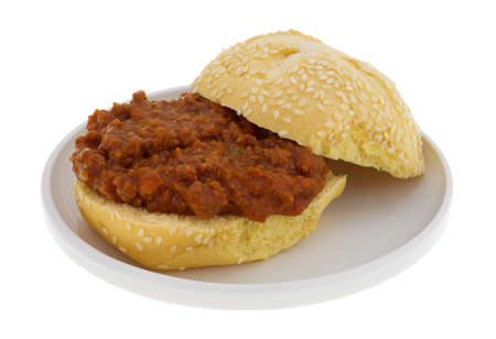 sloppy: A sesame seed roll with sloppy joe mix open on a small plate isolated on a white background. Stock Photo