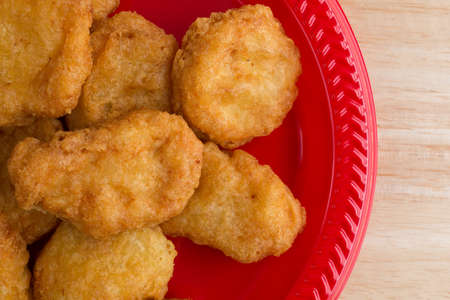 chicken nuggets: Top close view of a serving of chicken nuggets on a red plate on a wood table top illuminated with window light. Stock Photo