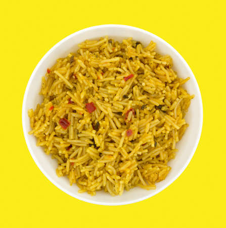 inexpensive: Top view of a bowl of Mexican rice on a bright yellow background.