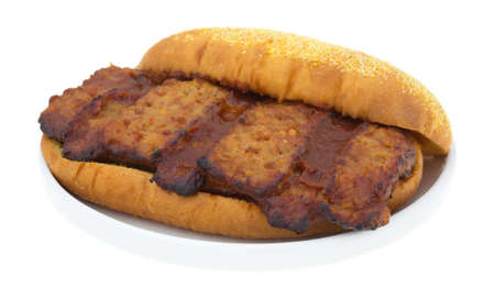 pork rib: A cooked pork rib sandwich with barbecue sauce made with a white bun on a small plate atop a white background.