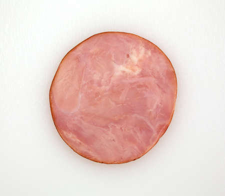 Top view of a round slice of ham on a white cutting board illuminated by natural light. Stock fotó