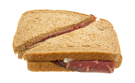 inexpensive: A roast beef sandwich sliced in half with white cheese and mayonnaise isolated on a white background. Stock Photo