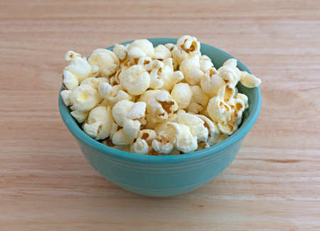 popcorn bowls: A small bowl filled with a serving of white cheddar cheese flavored popcorn on a wood counter top illuminated with natural light. Stock Photo