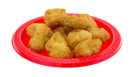 chicken nuggets: A serving of chicken nuggets on a red plate isolated on a white background.